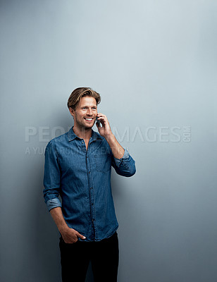 Buy stock photo Studio shot of a handsome young man using his cellphone while standing against a grey background