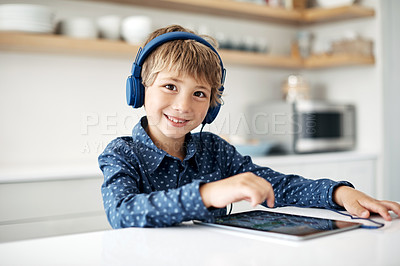 Buy stock photo Portrait of an adorable little boy wearing headphones while using a digital tablet at home