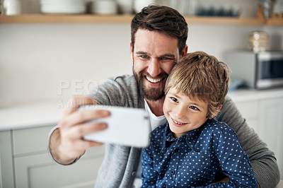Buy stock photo Shot of a father and his little son taking selfies together at home