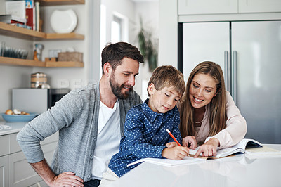 Buy stock photo Shot of a young man and woman helping their adorable son with his schoolwork at home