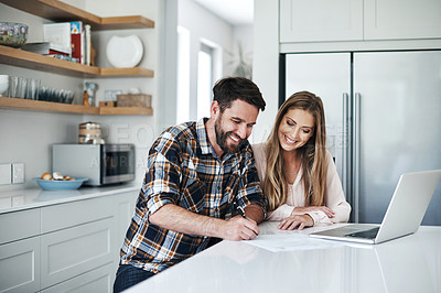Buy stock photo Shot of a young couple using a laptop and going through paperwork at home