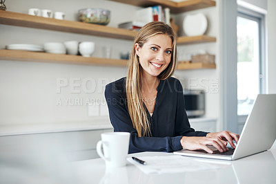 Buy stock photo Shot of an attractive young woman using a laptop on the kitchen counter at home