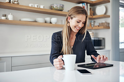 Buy stock photo Shot of an attractive young woman using a digital tablet on the kitchen counter at home
