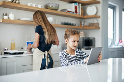 Buy stock photo Shot of an adorable little girl using a tablet while baking with her mother in the kitchen at home