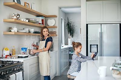 Buy stock photo Shot of an adorable little girl using a tablet while baking with her beautiful mother in the kitchen at home