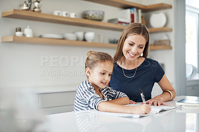 Buy stock photo Shot of an adorable little girl doing schoolwork with her beautiful mother at home