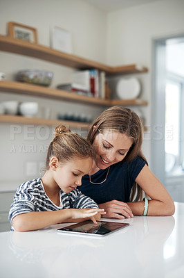 Buy stock photo Shot of an adorable little girl using a tablet with her beautiful mother at home