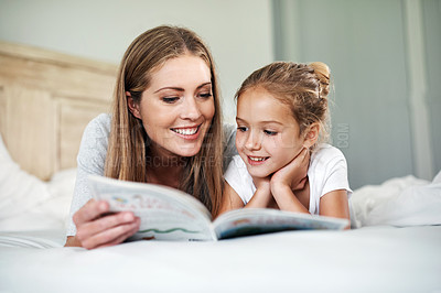 Buy stock photo Shot of a young beautiful mother reading a book to her adorable daughter in bed at home