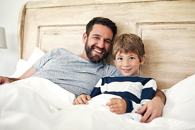 Buy stock photo Portrait of a father and his little son bonding together in bed at home