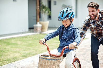 Buy stock photo Shot of a father teaching his little son how to ride a bicycle outdoors