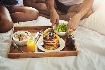 Buy stock photo High angle shot of an unrecognizable couple enjoying breakfast in bed together at home