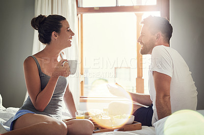 Buy stock photo Cropped shot of a happy young couple enjoying breakfast in bed together at home