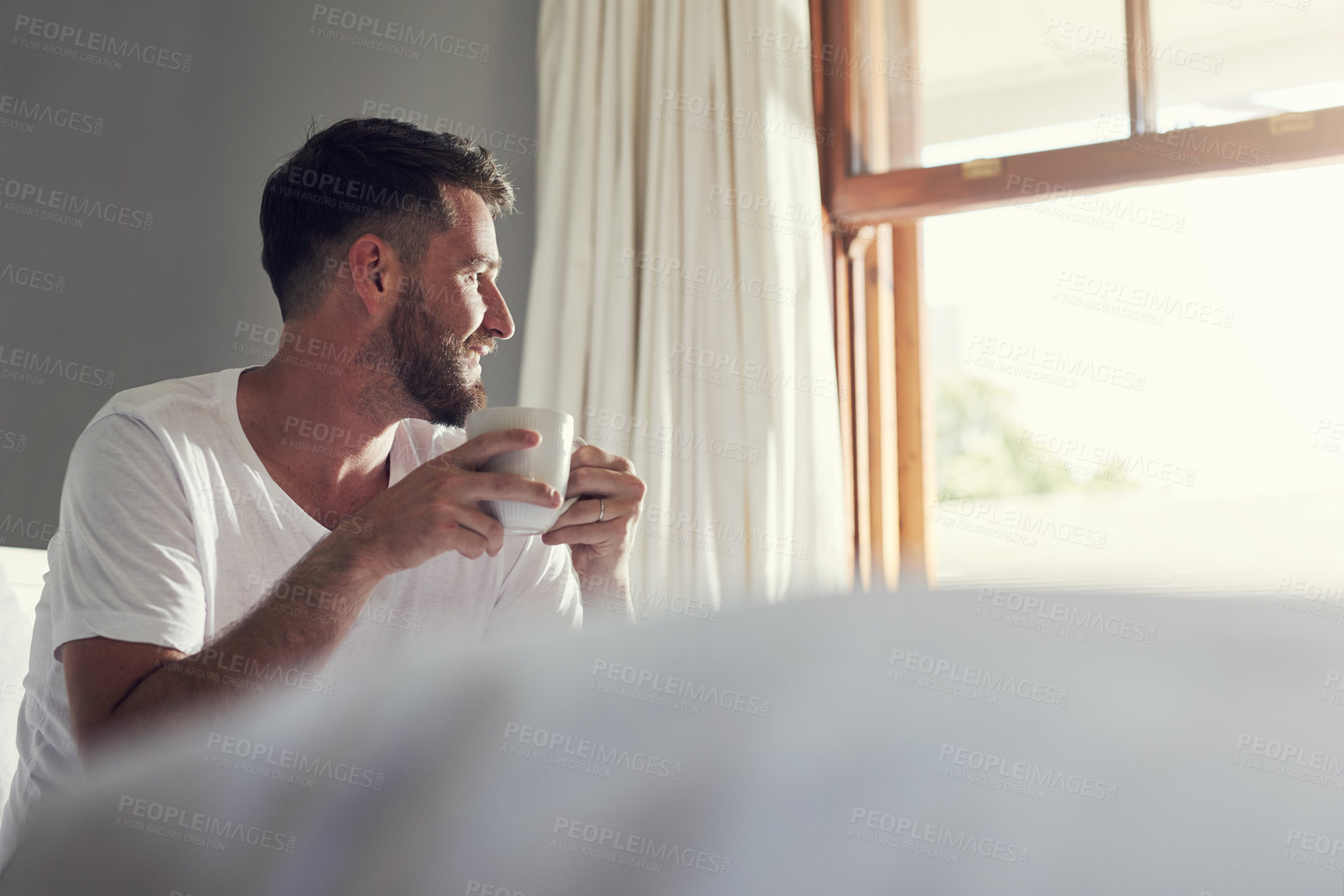 Buy stock photo Cropped shot of a handsome  young man drinking coffee in the bedroom at home