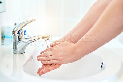 Buy stock photo Closeup shot of an unrecognizable woman washing her hands in the basin in the bathroom at home