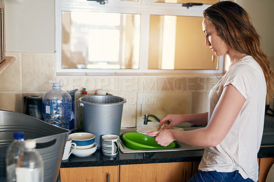 Buy stock photo Cropped shot of a beautiful young woman doing dishes and trying to save water in the kitchen at home