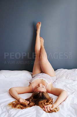 Buy stock photo Full length shot of an attractive young woman lying on her bed while in her pyjamas