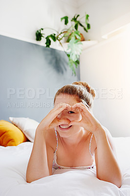 Buy stock photo Full length portrait of an attractive young woman looking through a heart shaped gap between her hands while lying on her bed