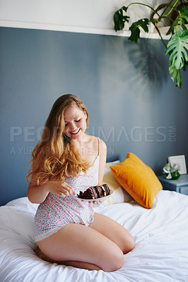 Buy stock photo Shot of a cheerful young woman enjoying a piece of cake while being seated on her bed at home during the day
