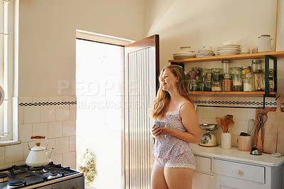 Buy stock photo Shot of a cheerful young woman enjoying a cup of coffee while standing in the kitchen at home during the day