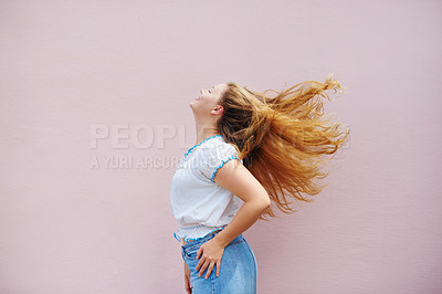 Buy stock photo Cropped shot of a beautiful young woman tossing her hair and posing against a pink wall outside