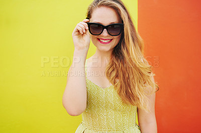 Buy stock photo Portrait of a beautiful young woman posing against a bright yellow and orange wall outside