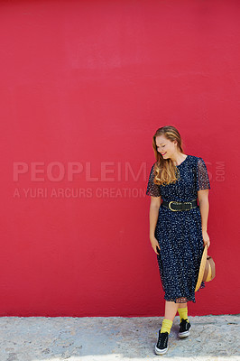 Buy stock photo Shot of a beautiful young woman posing against a red wall outside