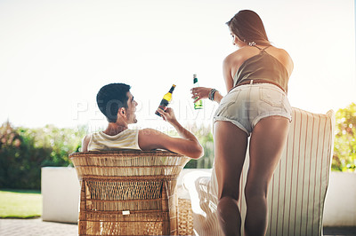 Buy stock photo Rearview shot of an affectionate young couple cheersing while drinking beer on their patio
