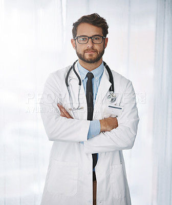 Buy stock photo Portrait of a confident young male doctor standing with his arms folded inside of a hospital during the day