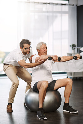 Buy stock photo Full length shot of a young male physiotherapist working with a senior male patient