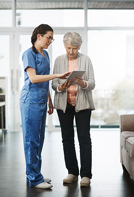 Buy stock photo Full length shot of a young female nurse showing her senior female patient something on a digital tablet