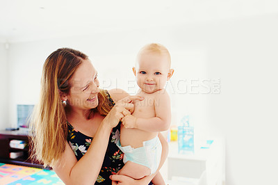 Buy stock photo Portrait of a young woman carrying her adorable baby girl at home