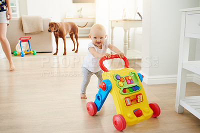 Buy stock photo Shot of an adorable baby girl playing with a toy walker at home
