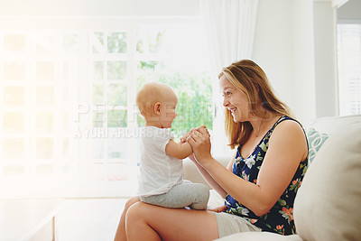 Buy stock photo Shot of a young woman relaxing with her adorable baby girl on the sofa at home