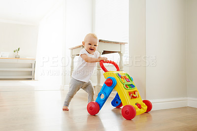 Buy stock photo Portrait of an adorable baby girl playing with a toy walker at home