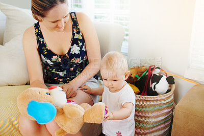 Buy stock photo Shot of an adorable baby girl and her mother playing with a teddy bear at home