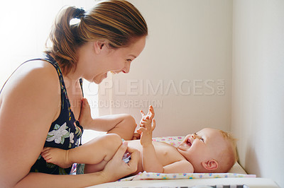 Buy stock photo Shot of a young woman changing her adorable baby girl's diaper on a table at home