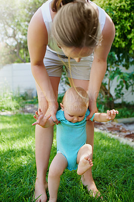 Buy stock photo Shot of an adorable baby girl learning to walk with help from her mother in the backyard
