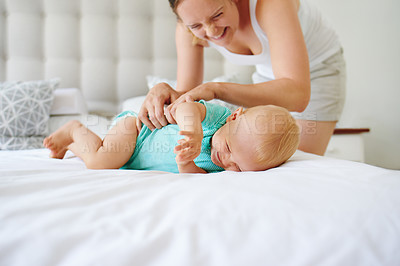 Buy stock photo Shot of an adorable baby girl playing together with her mother on the bed at home
