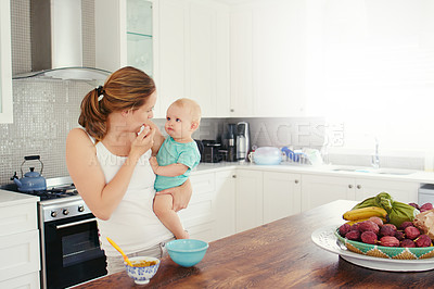 Buy stock photo Shot of a young woman feeding her adorable baby girl at home
