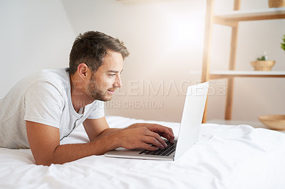 Buy stock photo Shot of a young man using a laptop on his bed at home