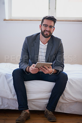 Buy stock photo Full length portrait of a handsome young businessman working on a tablet while sitting on his bed at home