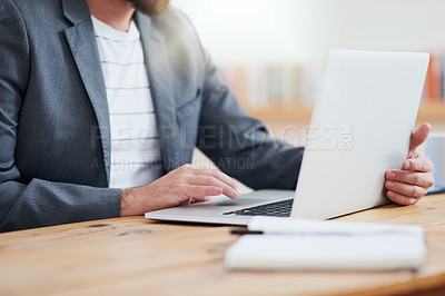 Buy stock photo Cropped shot of an unrecognizable businessman working on his laptop while sitting in the home office