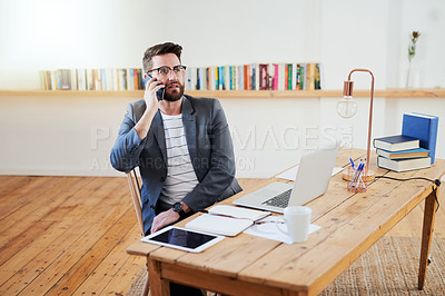 Buy stock photo High angle shot of a handsome young businessman making a phonecall while sitting in the home office