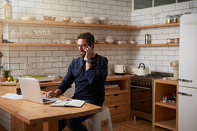 Buy stock photo Cropped shot of a handsome young businessman making a phonecall while sitting in the kitchen at home