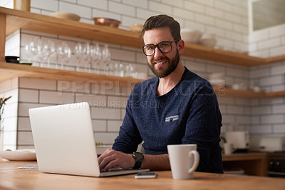 Buy stock photo Cropped portrait of a handsome young businessman working on his laptop while sitting in the kitchen at home