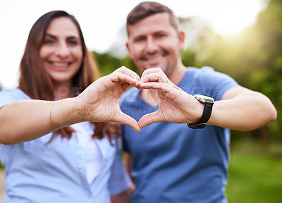 Buy stock photo Portrait of a cheerful young couple forming a heart together with their hands while standing outside in a park during the day
