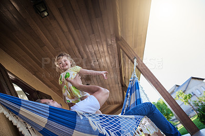 Buy stock photo Shot of a father and his little daughter bonding together on a hammock outdoors