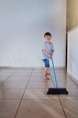 Buy stock photo Portrait of an adorable little boy using a broom to sweep the floor at home