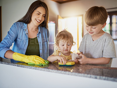 Buy stock photo Shot of a mother and her two little children doing chores together at home