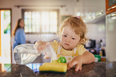 Buy stock photo Shot of a little girl holding a bottle of cleaning detergent with her mother in the background at home